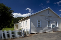 Painted_Corrugated_Iron_and_Weatherboard_Community_at_Colville_Coromandel_Peninsula_Established_in_1931_with_distinctive_picket_fence_and_Pohutukawa_tree_alongs