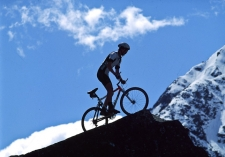 Extra_Fit_Mountain_Biker_wearing_protective_helmet_Mountan_Biking_in_the_Mountains_surrounded_by_Rock_Ice