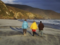 Three_adult_figures_colourfully_dressed_striding_along_remote_sandy_beach_with_stormy_surf_and_breakers_near_Cape_Saunders_Dunedin