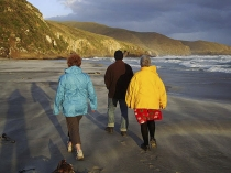 Three_adult_figures_colourfully_dressed_walking_along_remote_sandy_beach_with_stormy_surf_and_breakers