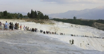 Stream_of_tourists_on_pink_and_white_silica_terraces_near_Pamukkale_Turkey