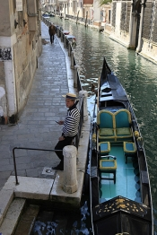 Gondolier_usin_Cell_phone_to_text_new_clients_alongside_canal_in_Venice