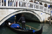 Venetian_Gondola_Gondolier_passing_underneath_arched_bridge_in_Venice