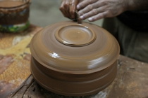 Artisan_potter_making_pot_from_brown_clay_using_wheel_and_traditional_methods